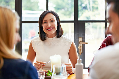 Buy stock photo Shot of a group of friends talking together while enjoying a home-cooked dinner