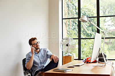 Buy stock photo Shot of a young man talking on the phone while working in his home office