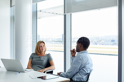 Buy stock photo Shot of two colleagues having a meeting in an office