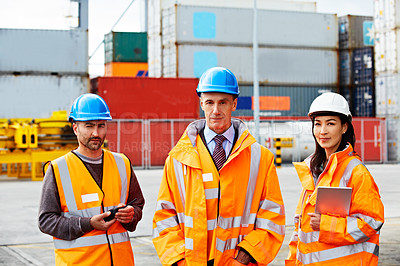 Buy stock photo Portrait of three coworkers in protective workwear standing on a large commercial dock