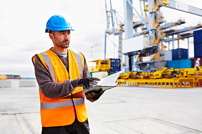 Buy stock photo Shot of a young man in workwear going through paperwork while standing on a dock