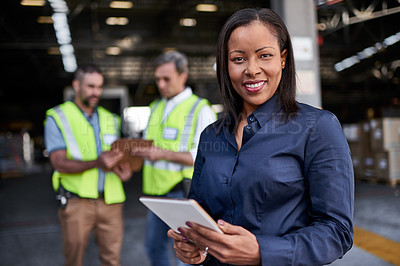 Buy stock photo Portrait of a warehouse manager holding a digital tablet with workers in the background