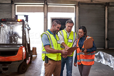 Buy stock photo Shot of three workers talking togetherover a clip inside of a warehouse