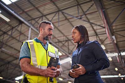 Buy stock photo Shot of two coworkers talking together over a barcode reader while standing in a large warehouse