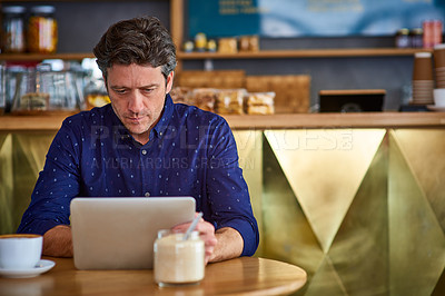 Buy stock photo Shot of a man working on a digital tablet in a cafe