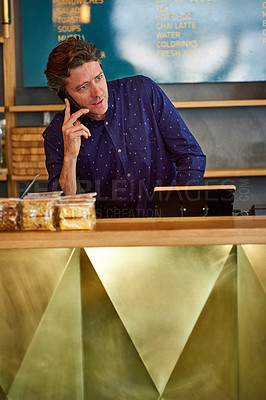 Buy stock photo Shot of a man talking on the phone while standing behind a counter in a cafe