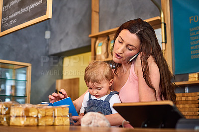 Buy stock photo Shot of a woman talking on the phone in a bakery with her little girl next to her on the counter