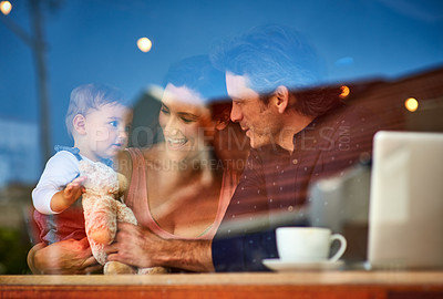 Buy stock photo Shot of a loving couple with their baby daughter sitting in a cafe
