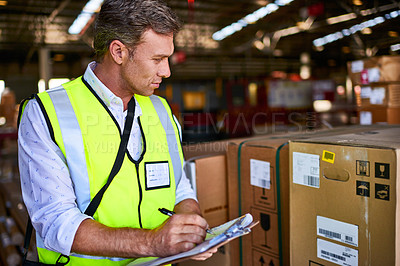 Buy stock photo Shot of a warehouse worker standing in a large warehouse holding a clipboard