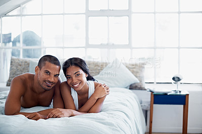 Buy stock photo Portrait of a young couple lying on their bed at home