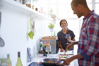 Buy stock photo Shot of a young couple enjoying cooking dinner together in their kitchen