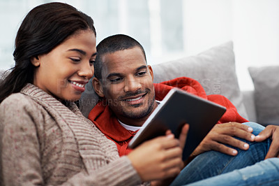 Buy stock photo Shot of a young couple using their tablet while sitting on the sofa at home