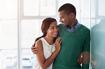 Buy stock photo Shot of an affectionate young couple standing arm in arm in their home