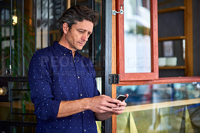 Buy stock photo Shot of a mature man texting on his cellphone wile standing in front of a cafe