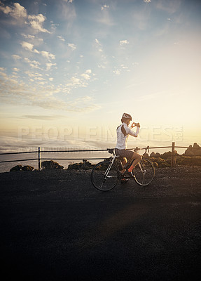Buy stock photo Full length shot of a young woman taking a photo while cycling in the mountains