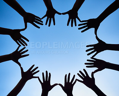 Buy stock photo Low angle shot of hands forming a circle against a bright blue sky