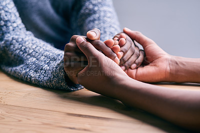 Buy stock photo Cropped shot of a two people holding hands in comfort on a table