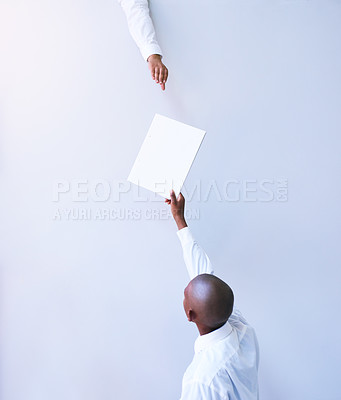 Buy stock photo Rearview shot of a young businessman handing a document to a colleague in an office