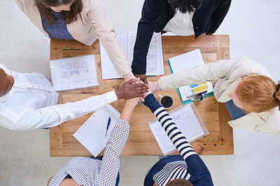 Buy stock photo High angle shot of a group of colleagues standing around a desk with their hands in a huddle