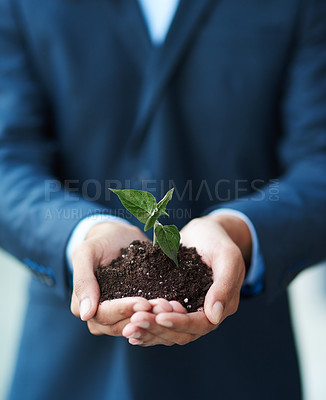 Buy stock photo Cropped shot of a businessman holding a plant growing in soil