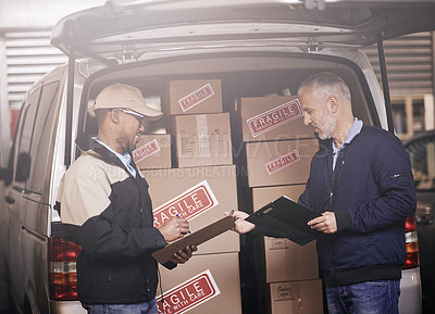 Buy stock photo Shot of two delivery men having a discussion next to a van filled with boxes