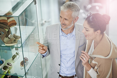 Buy stock photo Shot of a couple window shopping in a mall