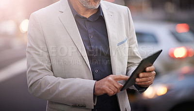 Buy stock photo Closeup of a mature businessman using a digital tablet outside
