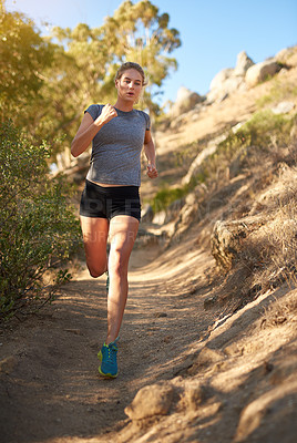 Buy stock photo Shot of a young woman out for a trail run