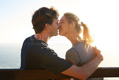 Buy stock photo Shot of a loving couple sitting on a bench overlooking the ocean