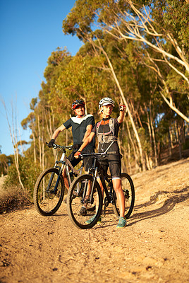 Buy stock photo Shot of a woman pointing towards something while out for a bike ride with her boyfriend