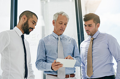 Buy stock photo Shot of a group of colleagues working on a digital tablet in an office
