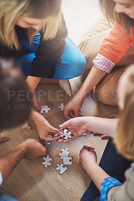 Buy stock photo Shot of a group of people building a puzzle together