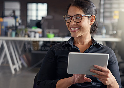 Buy stock photo Shot of a businesswoman using her digital tablet in an office