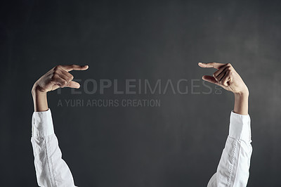 Buy stock photo Shot of hands pointing to each other against a dark background