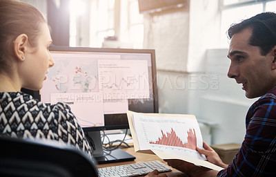 Buy stock photo Shot of coworkers going over paperwork together in a modern office