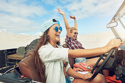 Buy stock photo Shot of two young friends going on a sand boarding road trip in the desert