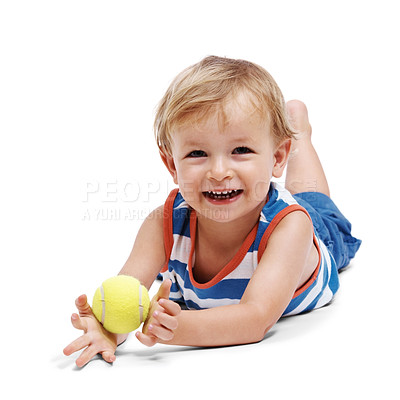 Buy stock photo Portrait of a happy little adorable boy lying on floor and playing with tennis ball over white background