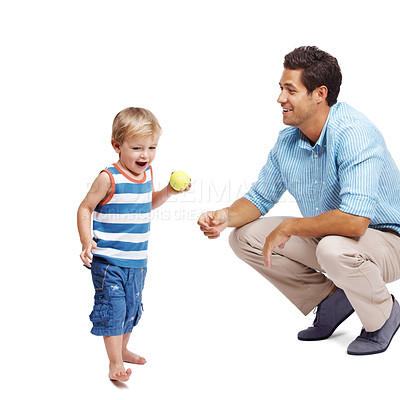 Buy stock photo Young father and his little son holding a tennis ball playing together over white background