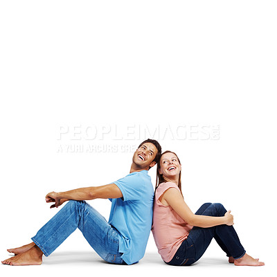 Buy stock photo Portrait of a young couple sitting back to back and smiling isolated over white background - Copyspace