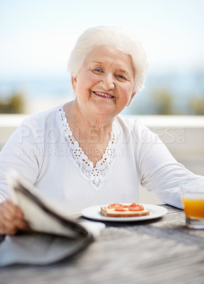 Buy stock photo Portrait of a happy mature woman having breakfast and reading the paper