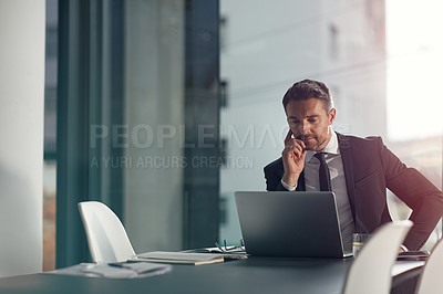 Buy stock photo Shot of a businessman working on a laptop in an office