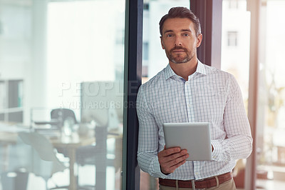 Buy stock photo Portrait of a businessman using a digital tablet in an office