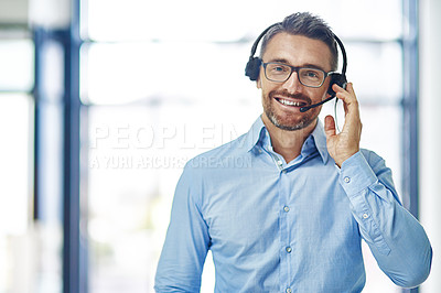 Buy stock photo Portrait of a friendly mature businessman wearing a headset in an office