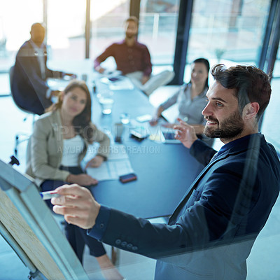 Buy stock photo Cropped shot of a businessman giving a presentation to coworkers in a boardroom meeting