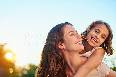 Buy stock photo Cropped shot of a mother giving her daughter a piggyback ride outside