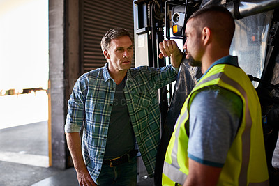 Buy stock photo Shot of two coworkers talking together inside a large warehouse