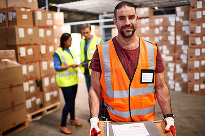 Buy stock photo Portrait of a worker standing in a large warehouse full of boxes with colleagues in the background