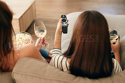 Buy stock photo Rearview shot of two friends sitting on a sofa drinking wine and watching a movie on tv