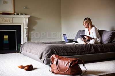 Buy stock photo Shot of a mature businesswoman sitting on a hotel bed using a laptop and digital tablet
