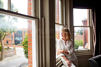 Buy stock photo Shot of an attractive mature woman looking through her living room window